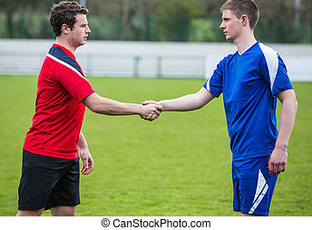 Football players in blue and red shaking hands on a clear...