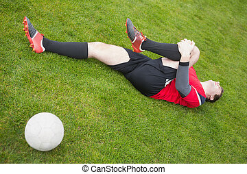 Football player in red lying injured on the pitch on a clear...