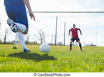 Goalkeeper in red ready to save a penalty on a clear day