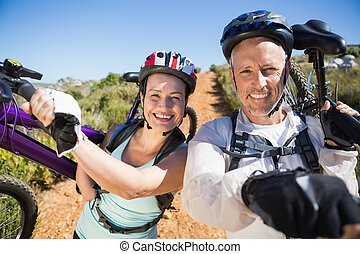 Active couple carrying their bikes on country terrain...