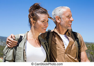 Hiking couple smiling together on mountain trail on a sunny...