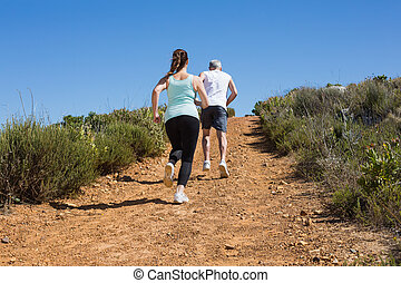 Fit couple running up mountain trail on a sunny day