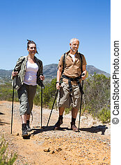 Happy hiking couple walking on mountain trail on a sunny day