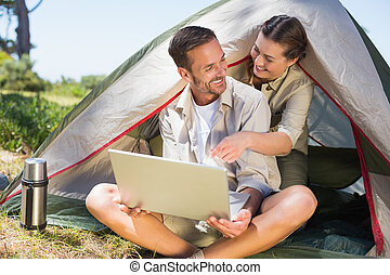 Outdoorsy couple looking at the laptop outside tent on a...