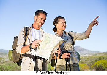 Hiking couple consulting the map in the countryside on a...