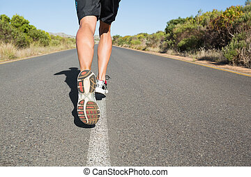 Fit man jogging on the open road on a sunny day