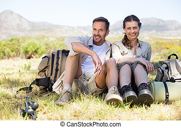 Happy hiking couple taking a break on mountain trail on a...