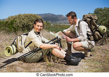 Hiking couple taking a break on country terrain on a sunny...