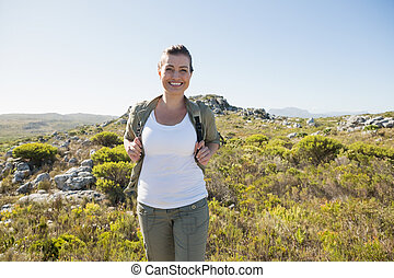 Pretty hiker smiling at camera on mountain terrain on a...