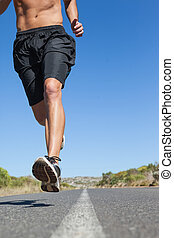 Shirtless man jogging on open road on a sunny day