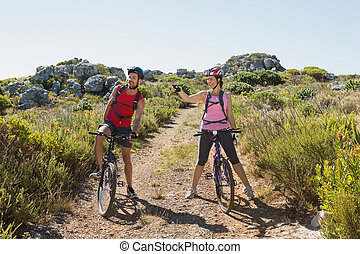 Active couple cycling in the countryside looking to the side