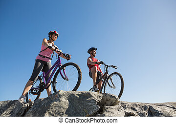 Active couple on a bike ride in the countryside on a sunny...