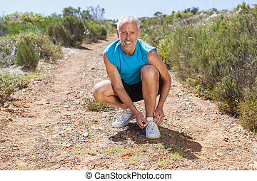 Smiling jogger tying his shoelace on mountain trail on a...
