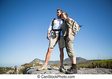 Hiking couple looking out over mountain terrain on a sunny...