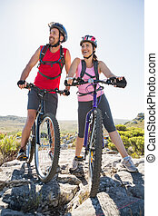 Fit cyclist couple looking ahead on mountain trail on a...