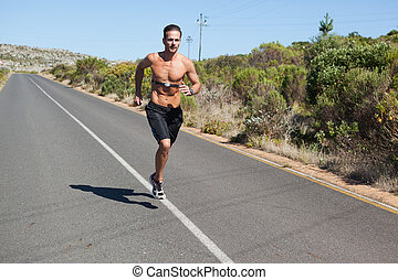 Athletic man jogging on open road with monitor around chest...