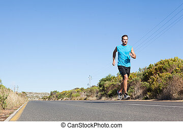 Athletic man jogging on the open road on a sunny day