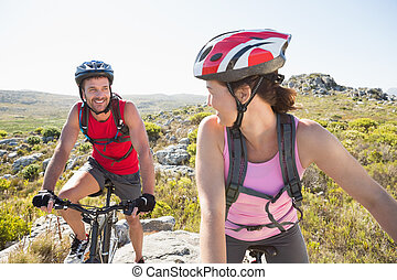 Fit cyclist couple riding together on mountain trail on a...