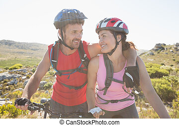 Fit cyclist couple smiling together on mountain trail on a...