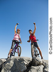 Fit cyclist couple cheering at the summit on a sunny day