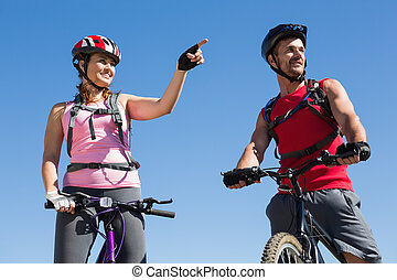 Fit cyclist couple standing at the summit on a sunny day