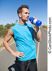 Athletic man on open road taking a drink on a sunny day