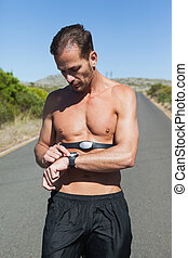 Athletic man on open road with monitor around chest on a...