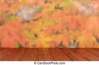 Empty wooden table over autumn leaves bokeh background....