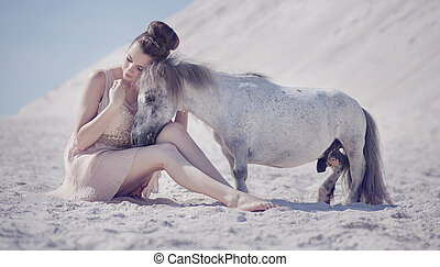 Pretty young woman hugging the pony