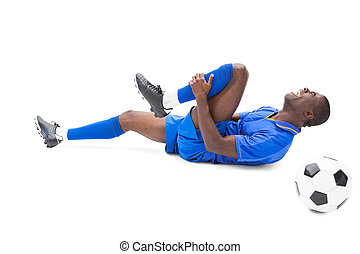 Injured football player lying on the ground on white...