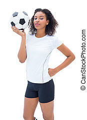 Pretty football fan in white holding ball on white...
