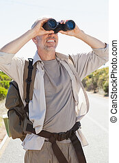 Hiker standing on road looking through binoculars on a sunny...