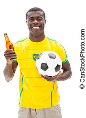 Happy brazilian football fan holding ball and beer on white...