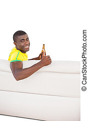 Happy brazilian football fan sitting on couch with a beer