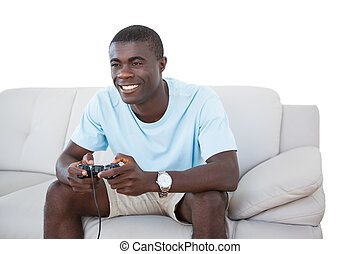 Smiling man sitting on couch playing video games on white...