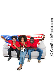 American football fans in red on the sofa on white...