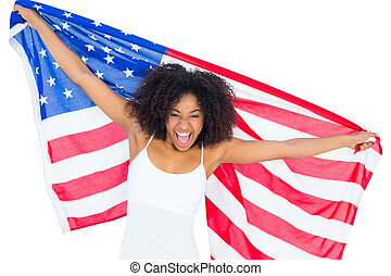 Pretty cheering girl in white top holding american flag on...