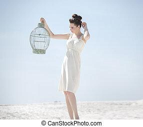 Elegant lady holding the golden cage - Elegant lady holding...