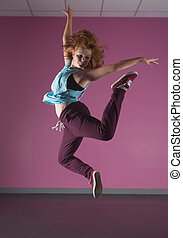 Pretty break dancer jumping up in the dance studio