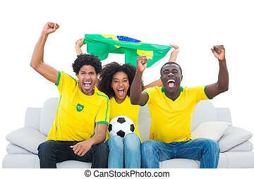 Excited football fans in yellow sit