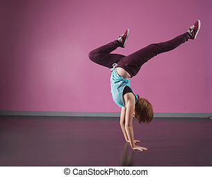 Pretty break dancer doing a handstand in the dance studio