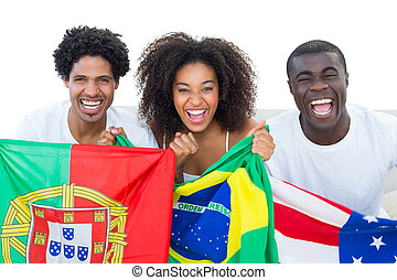 Happy football fans holding flags smiling at camera on white...