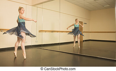 Beautiful ballerina dancing in front of mirror in the dance...