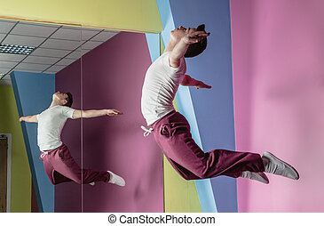 Cool break dancer mid air in front of mirror in the dance...