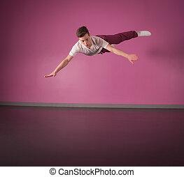 Cool break dancer mid air in the dance studio