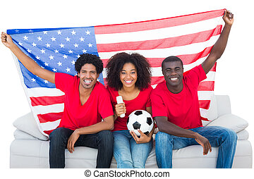Happy football fans in red sitting on couch with usa flag on...