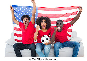 Cheering football fans in red sitting on couch with usa flag...