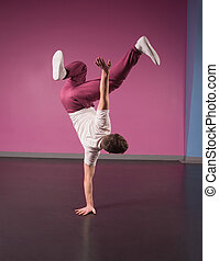 Cool break dancer doing handstand on one hand in the dance...