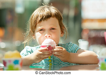 girl eating ice cream at outdoor cafe