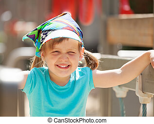 Portrait of laughing child at playground in sunny summer day...
